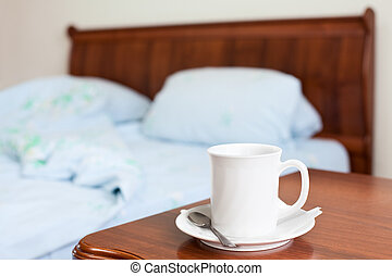 White cup on a bedside nightstand in the bedroom