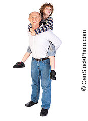 Grandfather giving grandson piggy-back against white...