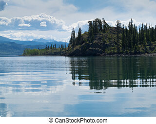Yukon wilderness reflected on calm lake - Green forested...