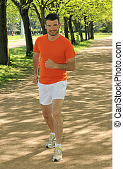 Young man jogging in nature in sportive outfit