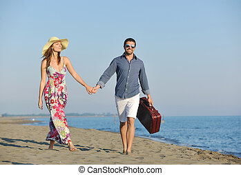 couple on beach with travel bag representing freedom and...