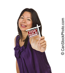 Attractive Multiethnic Woman Holding Small For Sale Real Estate Sign in Hand Isolated on White Background.