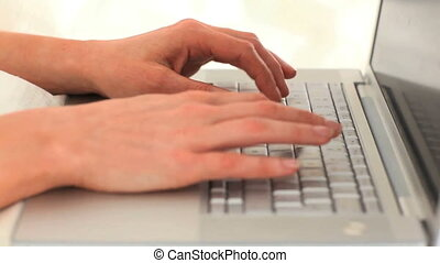 Woman\'s hands typing on a computer