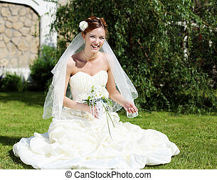 Portrait of a young bride in a white dress with a bouquet of...