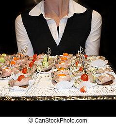 Waitress serving finger food.