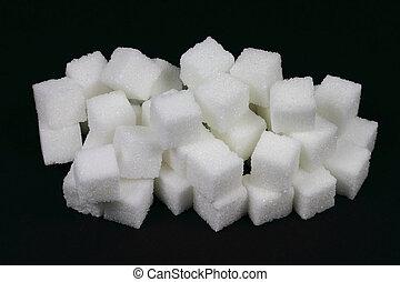 Spilled Cubes Sugar on pile over black.