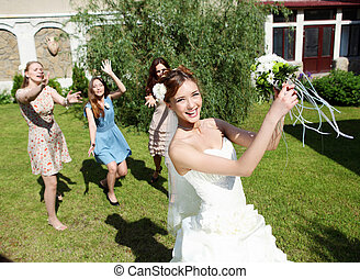 Young bride in white wedding dress throws a bouquet of...