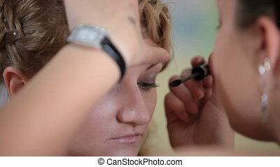makeup eyelashes - makeup artist paints eyelashes a young...