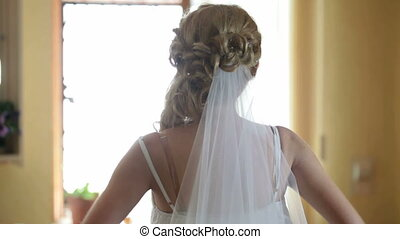 morning of the wedding day - Bride sits before a mirror in...