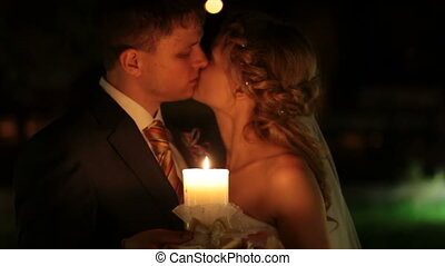 kissing by candlelight - just married couple kissing by...
