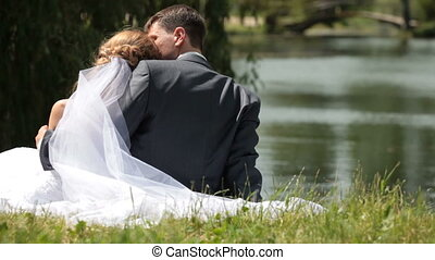just married couple sitting embraced near a pond