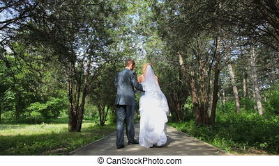 newlyweds go away hugging - newlyweds go away on a shady...