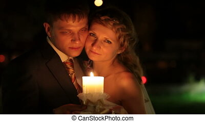 wedding candle - bride and groom standing embraced at night...