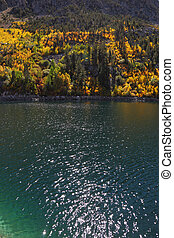 Solar autumn midday - Mountain fishing lake with transparent...