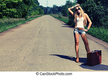 road - Pretty young woman hitchhiking along a road.