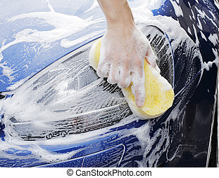 Car wash - man washing a soapy blue car with a yellow...