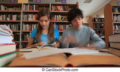 Working in library - Teenage boy and girl working together...