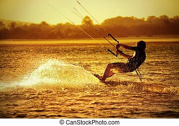 Kite boarder on ocean at sunset - sport