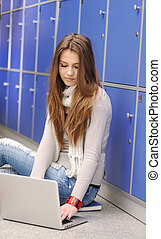 Beautiful female student sitting on ground with laptop