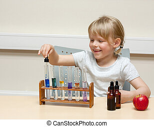 Cute little girl playing with chemistry; using different indicators (lakmus and BTB) to produce color reactions in acids and bases