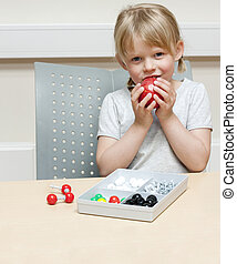 Cute little girl playing with a molecule building set, eating an apple