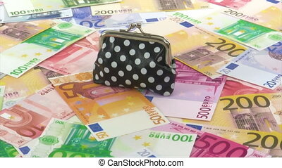 Cost of living - Purse filled with euro coins rotating on...