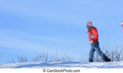 Winter fun - Happy family running on snow in winter
