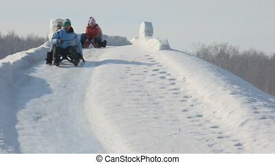 Family on sledges - Happy parents and their children riding...