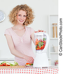 Pretty blonde woman using a mixer in the kitchen in her...