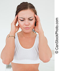 Woman having a headache against a white background