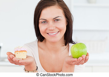 Close up of a cute woman with an apple and a piece of cake