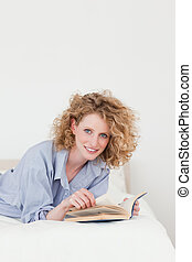 Attractive blonde woman reading a book while lying on her bed