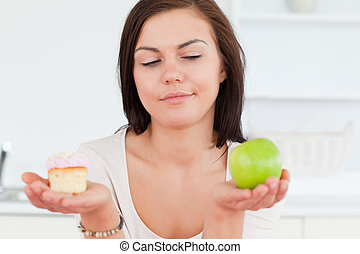Close up of a cute brunette with an apple and a piece of cake