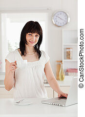 Beautiful brunette woman holding a cup of coffee while relaxing with her laptop in the kitchen