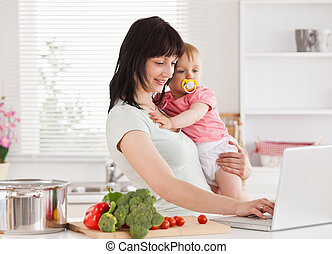Good looking woman holding her baby in her arms while...