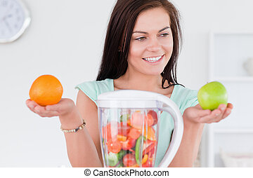 Charming woman with a blender and fruits looking at an apple