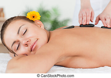 Delighted woman having a hot stone massage