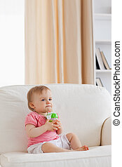 Lovely blond baby playing with a ball while sitting on a sofa