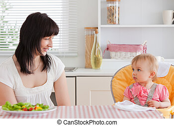 Gorgeous brunette woman having a meal with her baby while sitting in the kitchen