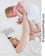 Gorgeous brunette woman playing with her baby while lying on...