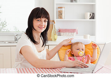 Beautiful brunette woman relaxing with her laptop next to her baby while sitting in the kitchen