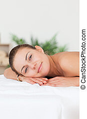 Portrait of a woman lying on her belly looking at the camera