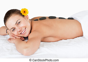 Smiling woman having a hot stone massage