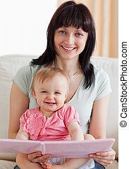 Beautiful woman holding her baby and a book in her arms...
