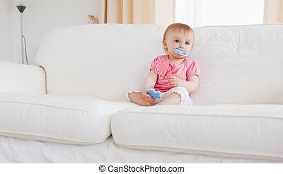 Lovely blond baby playing with puzzle pieces while sitting on a sofa in the living room
