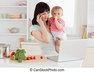 Good looking brunette woman on the phone while holding her...