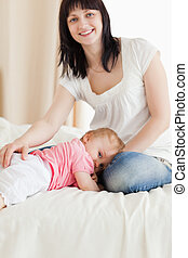 Cute brunette woman posing while her baby is lying on a bed