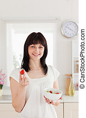 Pretty brunette female eating a cherry tomato while holding...