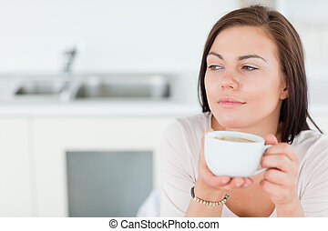 Close up of a smiling dark-haired woman having a coffee