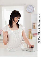 Attractive brunette woman holding a cup of coffee while relaxing with her laptop in the kitchen